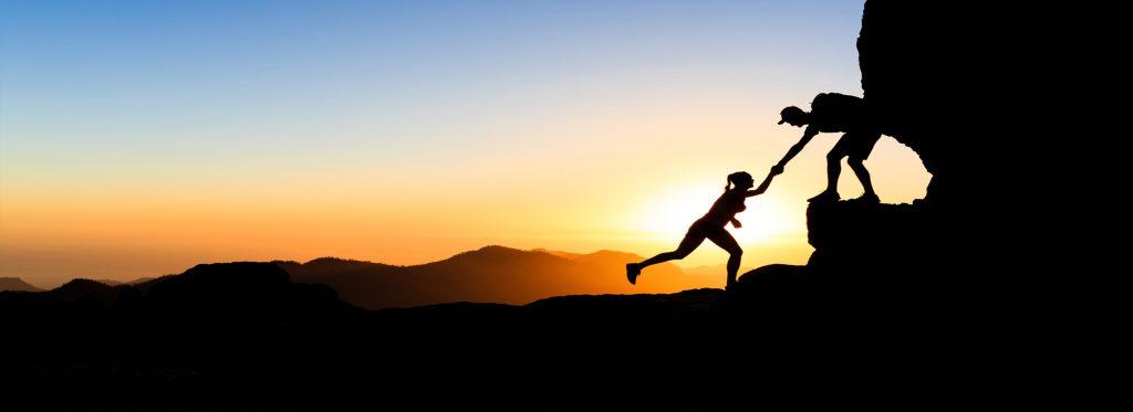 due scalatori che si aiutano a vicenda per raggiungere la vetta al tramonto